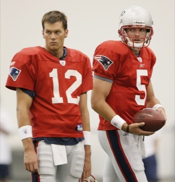 New England Patriots rookie quarterback Kevin O'Connell (5) walks past starting quarterback Tom Brady (12) during the first day of training camp.