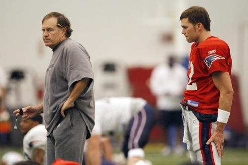 New England Patriots head coach Bill Belichick (left) watches his team practice alongside starting quarterback Tom Brady.