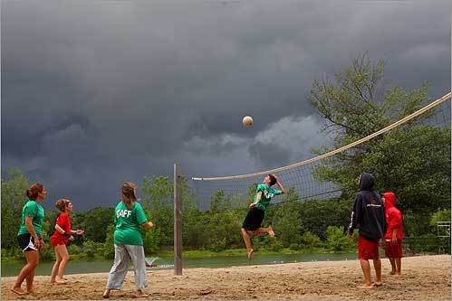 The staff at the Arlington Reservoir in Arlington played volleyball on an empty beachfront, as the threatening skies and weather kept swimmers away.