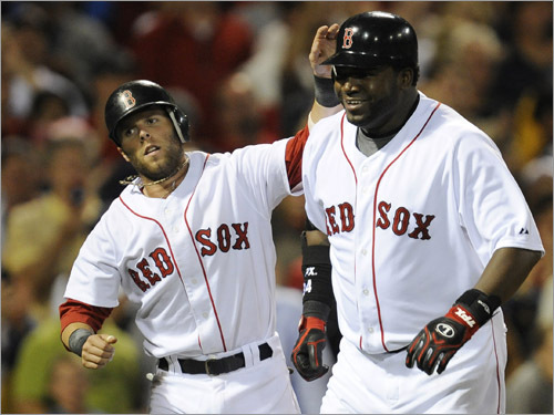 Red Sox second baseman Dustin Pedroia congratulates teammate David Ortiz after Ortiz hit a home run, driving in Pedroia during the fourth inning.