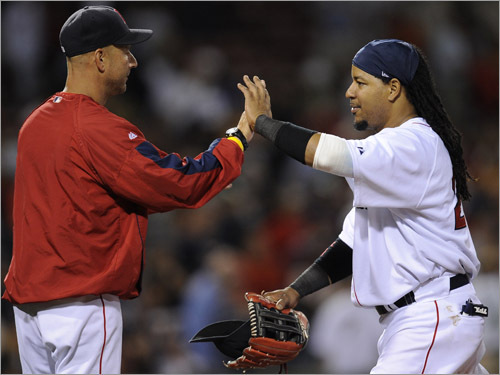 Red Sox manager Terry Francona high-fives left fielder Manny Ramirez after the Boston Red Sox defeated the New York Yankees.