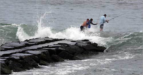 Fishermen struggle to maintain their balance in heavy surf at the end of a jetty on Block Island.