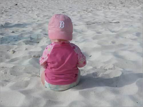 Sox fan Libby plays on the beach in sunny Aruba.
