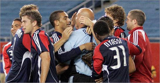 Teammates surround New England Revolution goalie Matt Reis after the Revolution beat the Houston Dynamo in a shootout in the SuperLiga final soccer match.