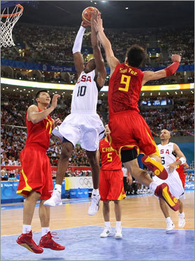 Kobe Bryant went up for a dunk between Yi Jianlian (11) and Sun Yue.