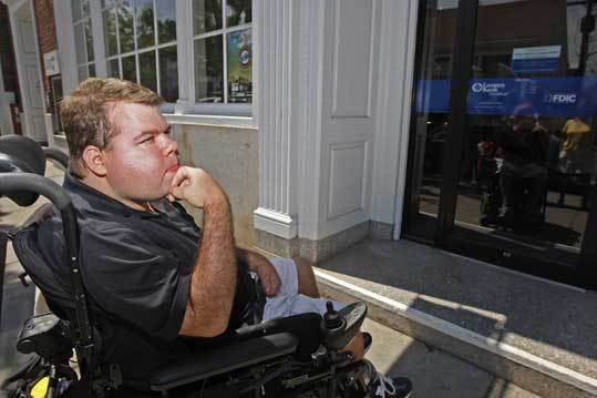 Kenny Cieplik at the front door of Eastern Bank in downtown Plymouth, which he is unable to enter because its step is too high.