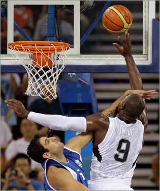 Dwayne Wade is hacked by Greece's Ioannis Bourousis on his way to the basket.