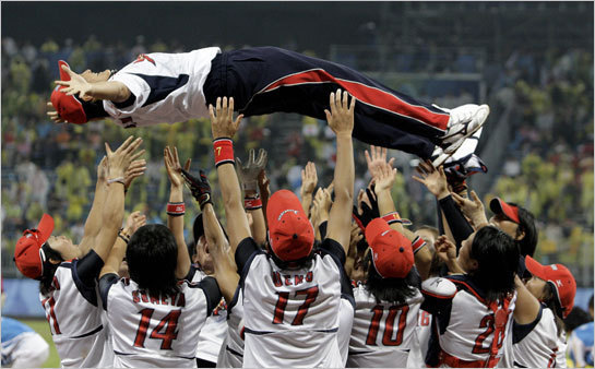 After handing the US its first loss in eight years, the Japanese women's softball team celebrates winning the gold medal by tossing their coach Haruka Saito in the air.