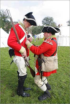 Joe Mallen (left) was helped with his uniform by John Keegan during a reenactment of a British encampment on Boston Common on Aug. 16, marking the 50th anniversary of the Freedom Trail.