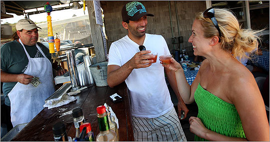 Zach Vitas and Katie James, both of Charlestown, make a toast before chugging an oyster shot at the Beachcomber in Wellfleet.