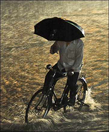 A man holds an umbrella and cycles through a flooded street as it rains in Hyderabad, India, Friday, Aug. 8, 2008.