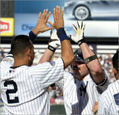 Jason Giambi (right) celebrated with teammate Derek Jeter after his hit drove in the winning run.