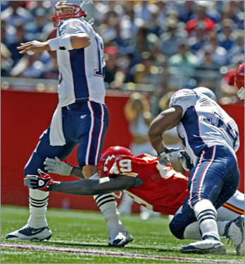 Patriots quarterback Tom Brady(left) was hit by Kansas City safety Bernard Pollard as he dropped back to pass during the first quarter.
