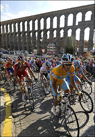 The Tour de France is more famous, but the Tour of Spain is one of three 'Grand Tours' on the cycling calendar. Astana rider and leader of the race Alberto Contador of Spain (in yellow jersey) and other riders cycle through the town of Segovia during stage 19 of the Tour of Spain or 'La Vuelta' cycling race between Las Rozas and Segovia, September 19, 2008.