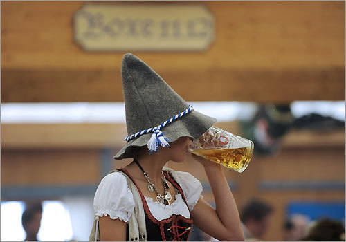 A woman drinks beer during the opening day of the festival. Beer at the festival comes from one of the tents containing Spaten, Lowenbrau, Augustiner, Hofbrau, Paulaner, and Hacker-Pschorr.