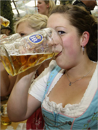 A woman wearing a traditional Bavarian Dirndl drinks beer during the opening ceremony.