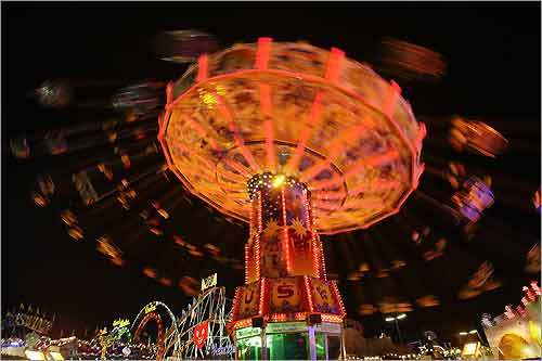 Visitors ride an amusement park attraction at the second evening of the Oktoberfest.