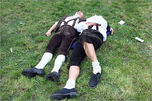 Two men in Bavarian costume take a nap on the ground.