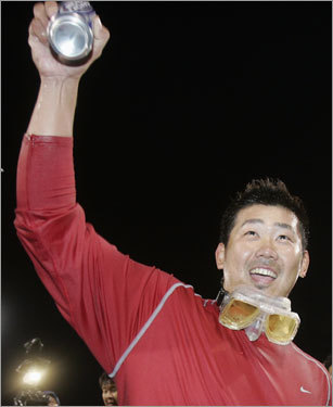 Goggles around his neck, Daisuke Matsuzaka holds up a beer during the postgame celebration.