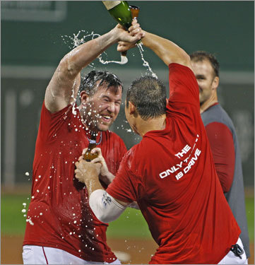 After the clinching victory, Red Sox players first celebrated in the clubhouse, then returned to the field to continue the party with the fans. Here Sean Casey douses Kevin Cash with champagne on the field.