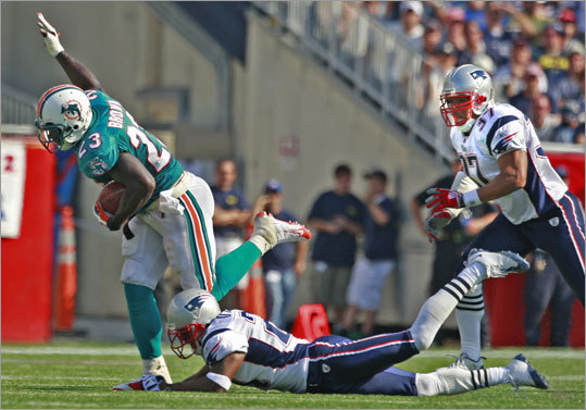 Dolphins running back Ronnie Brown breaks free from Patriots Deltha O'Neal enroute to a 62 yard touchdown run during fourth quarter action at Gillette Stadium on Sunday.