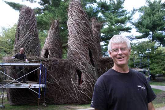 Artist Patrick Dougherty in front of his ''Twisted Sisters,'' a sculpture of twigs and branches at Wheaton College. Students at the college helped him put the piece together.