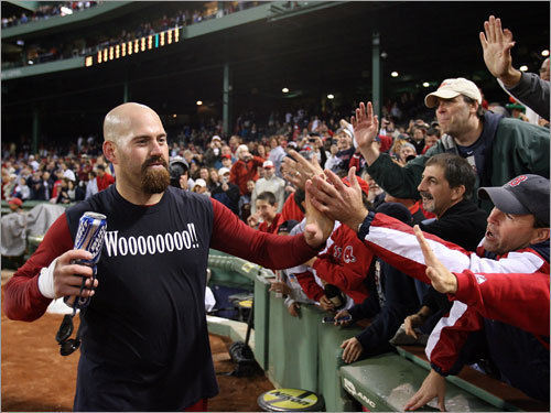 Kevin Youkilis, wearing a shirt appropriate for the occasion, celebrates with fans.