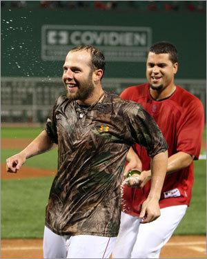 Manny Delcarmen sprays Dustin Pedroia with champagne.