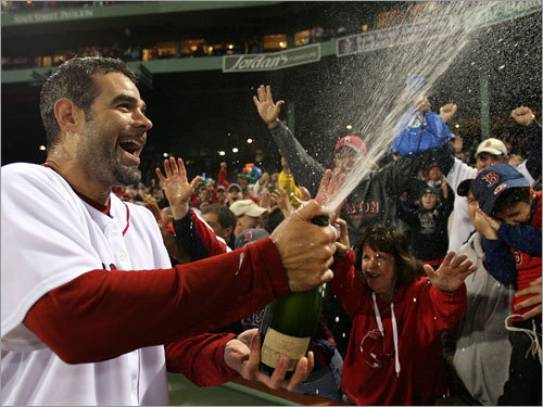Mike Lowell sprays fans with champagne as the Red Sox celebrated Tuesday night.