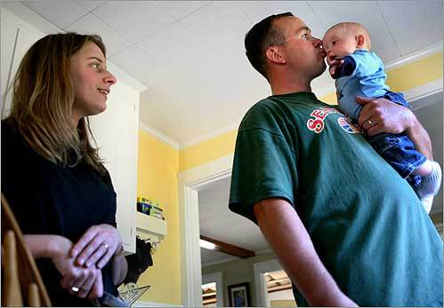 Benay Ames (left) with her husband Michael and their son, Ryan, 6 months, in their Braintree home Sept. 20. The economy is affecting the Ames. She said she has a secure job in healthcare, and her husband, a stone mason, is working, too. But he just lost his bid for membership in the Bricklayers and Masons Union. It can't find work for new members because of the weakened job market, Ames said.