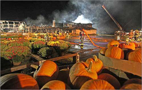 Firefighter Paul Domenichella gathered hoses after he and his colleagues battled a blaze that consumed the the Verrill Farm stand in Concord. The Verrill family, owners of the popular farmstand, have vowed to rebuild.