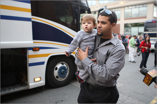 Red Sox pitcher Manny Delcarmen carried his young son to the team bus.