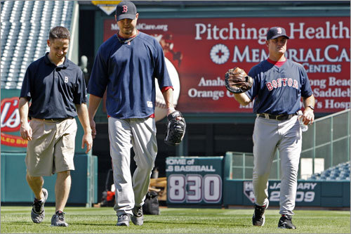 'Pitching Health', as the sign in rightfield says, may be the key to any post season success the Red Sox enjoy, particularly the status of staff ace Josh Beckett (center). He is shown as he walks off the field with Mike Reinhold (left) a memeber of the team's training staff, and pitching coach John Farrell (right) after he threw in the outfield in front of them before the start of Tuesday's workout.