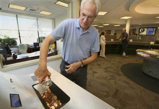 The Rev. Dick Hotchkin counts donated pennies at a bank.