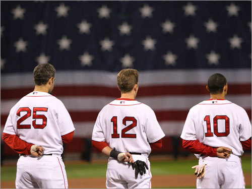 Red Sox players Mike Lowell (left), Jed Lowrie (center), and Coco Crisp (right) looked on during the national anthem.