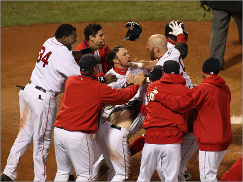 David Ortiz (34), Mark Kotsay (center), and Youkilis (center-right) surround Bay (losing his shirt in the bottom of the pile).