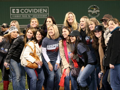 Red Sox wives, significant others, and friends pose for a celebration photo on the infield after the Game 4 win Monday night.