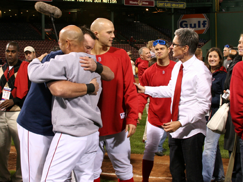 Sean Casey (left) hugs Red Sox manager Terry Francona after Game 4 while Red Sox owner John Henry (right) congratulates Justin Masterson on advancing to the ALCS.