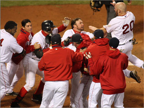 Youkilis (right) jumps into the crowd surrounding Bay at home plate.
