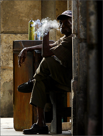 See more photography at Boston.com/photos A man who repairs lighters smokes a cigar as he waits for customers in a street in Havana, Monday, Sept. 29, 2008.
