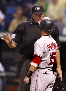 Dustin Pedroia (15) was sent back to third by home plate umpire Tim McClelland after attempting to score from first on a ground rule double off the bat of Kevin Youkilis (not pictured).