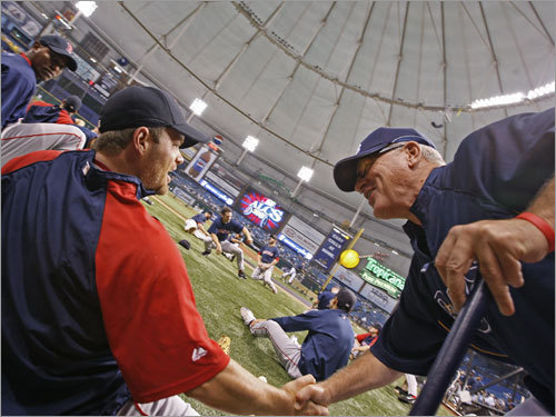 Tampa Bay Rays manager Joe Maddon (right) spoke with Red Sox pitcher Paul Byrd (center) during warmups.