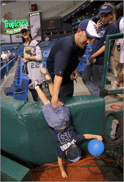 Rays fan Elijah Ferguson reaches down to touch the field before Game 1.