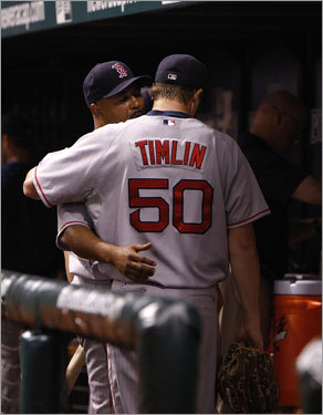 Red Sox pitcher Mike Timlin was given a consoling hug by Sox Coach Demarlo Hale in the dugout after Timlin gave up the winning run in the 11th inning.