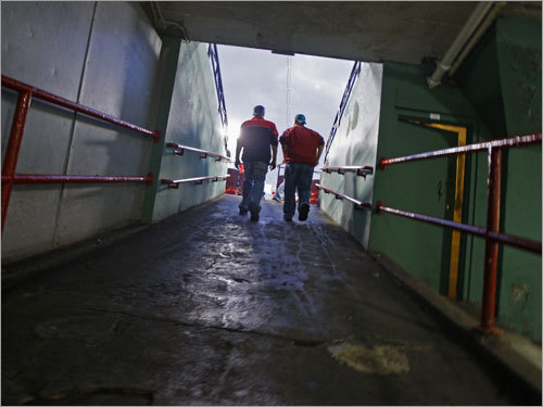 Two early arriving fans headed up a ramp to the stands along the first base side of Fenway Park.