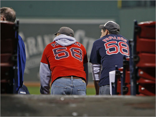 Two fans, each wearing a different color Jonathan Papelbon jersey, watched batting practice.