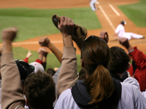 Fans cheer as Red Sox first baseman Mark Kotsay slides across the plate with the tying run in the eighth inning.