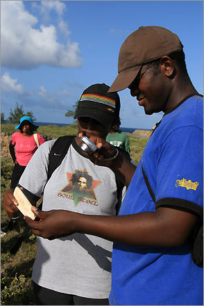 Hikers examine the remains of a shell tool on a trek through St John's Parish. Early Barbadian inhabitants carved their tools from shells, tossing the imperfect or damaged ones into the woods where they are still found centuries later.