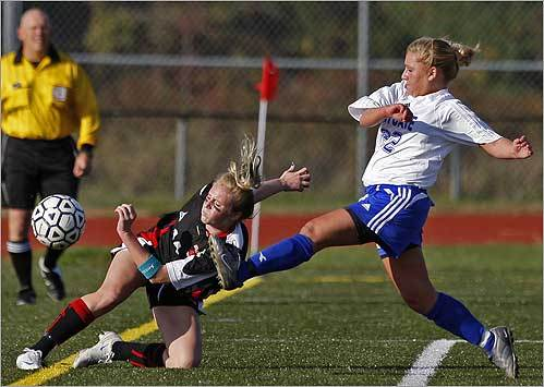 Whitman Hanson's Nicole Philbrook tried to clear the ball with defensive pressure from Scituate High's Alex Sarantos (No. 22) during first-half action at Scituate High School on Oct. 14. Whitman-Hanson defeated Scituate 1-0.