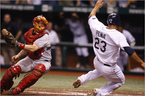 Jason Varitek (left) received the relay throw from right field but could not get the tag on the Rays' Carlos Pena (right) in the fourth inning.
